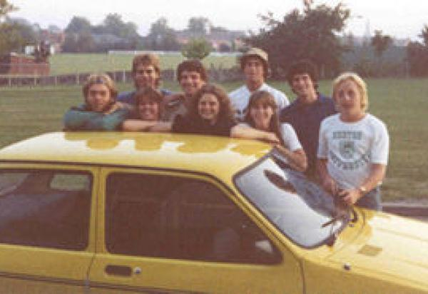 9 students standing behind yellow car