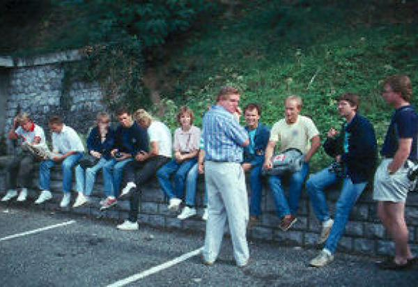 Mike Moss talking to students sitting on a roadside ledge