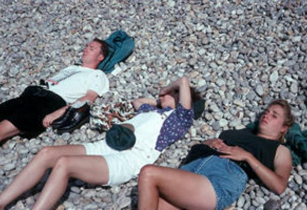 Three students laying on rocks in sun