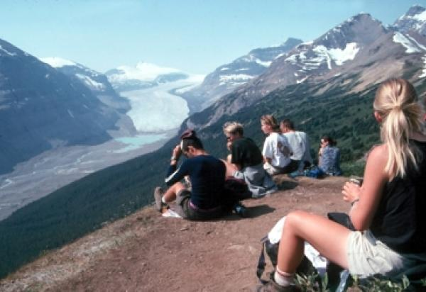 Students sitting hillside surrounded by mountains
