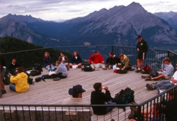 Students sitting on a deck, mountains in background