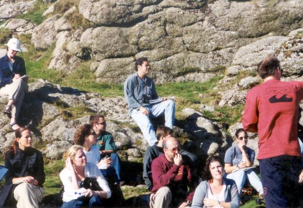 Students by big rock listening to lecture