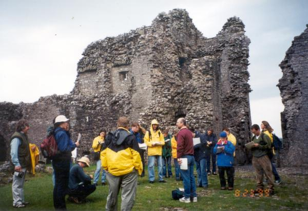 Students listening to lecture outside stone ruins