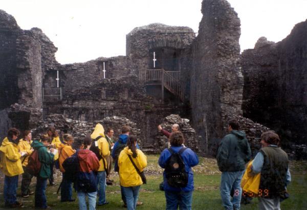Students in rain gear exploring stone ruins