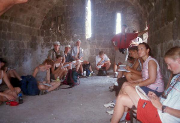 Students sitting in old stone building taking notes