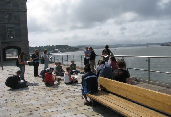 Students listening to lecture along ledge/waterside