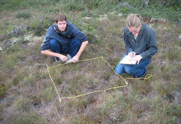 two students kneeling in field taking measurements