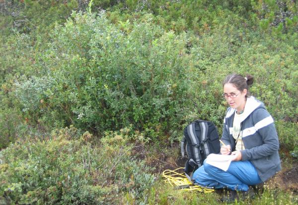 female student sitting in field collecting data
