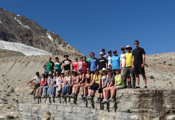 Class of 2013 sitting on rock ledge in mountains