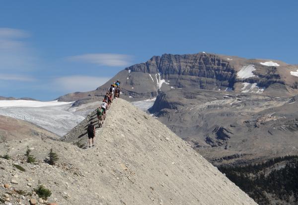 Students walking in a line along mountain ridge