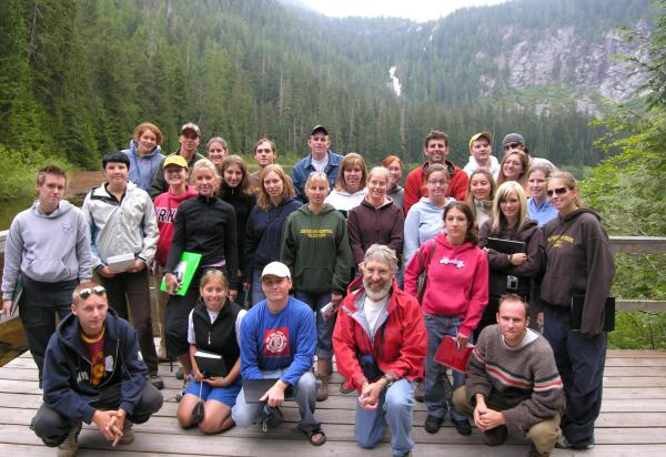 Group shot of class standing on deck mountains in background