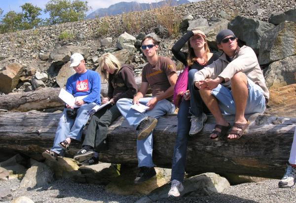 Five students sitting on a log, sunny day