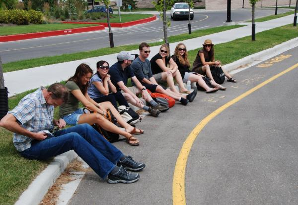 Row of students sitting curbside