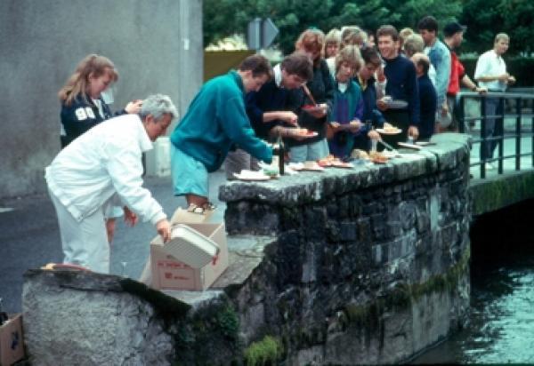 Students having lunch along ledge/waterside