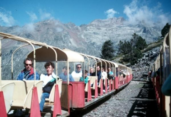 Students riding tram with mountains in background