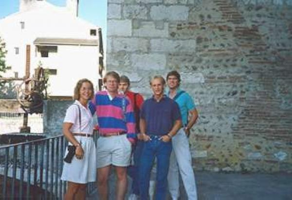 Five students in front of stone wall