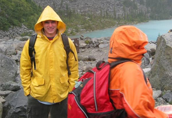two students in rain gear walking along rocky coast