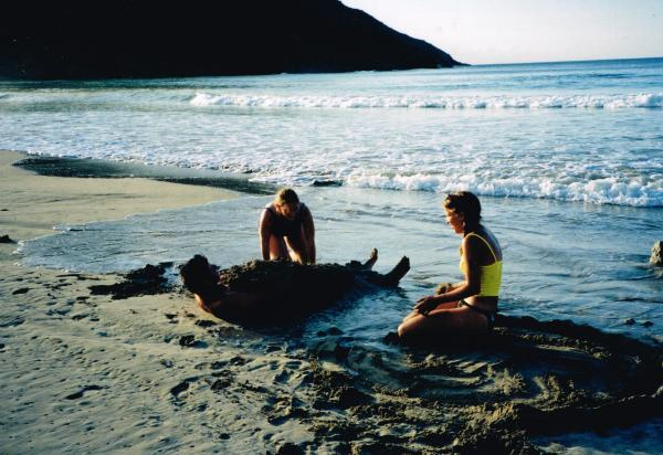 Two students burying another on beach