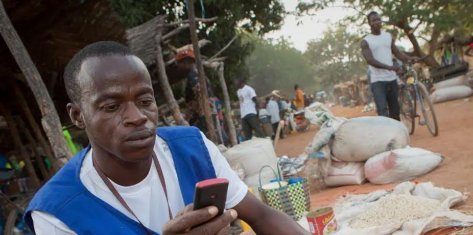 Scene from an African village with young man looking at his phone.